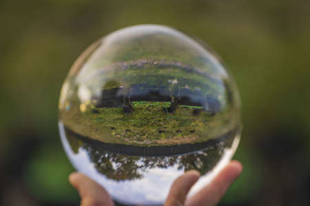 Photo pour Close up view of hand holding crystal ball with inverted image of green natural landscape. - image libre de droit