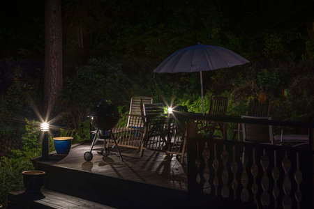 Photo for Beautiful view night of wooden patio of typical wooden Swedish house with table, chairs and sitting area with umbrella. Sweden. - Royalty Free Image