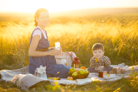 Pregnant mother and her cute little son outdoors. Happy family and healthy eating concept.