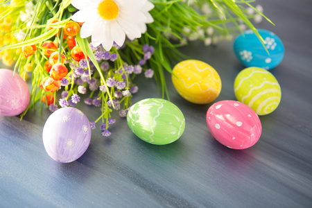 Photo pour Easter eggs and flowers on a gray wooden planks - image libre de droit