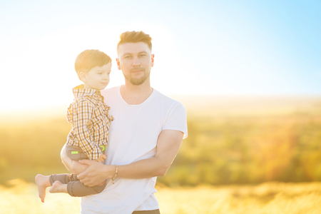 Photo for Happy father and son together having in the park on a warm sunny day. Family and love concept. - Royalty Free Image