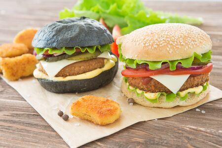 Delicious fast food. Craft beef burgers with vegetables. Flat lay on wooden textured background with sesame seeds.