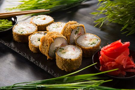 Photo for Set of fried sushi rolls with wasabi and ginger on a black background. Japanese oriental cuisine - Royalty Free Image