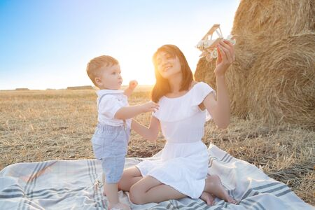 Photo pour Woman and her son playing with toy airplane . - image libre de droit