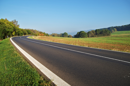 Empty asphalt road in countryside, bend of road, field in the background, forest on the horizon