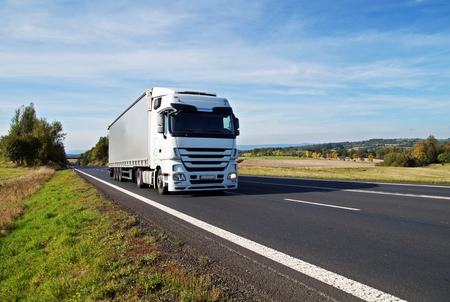 White truck travels on the asphalt road in the countryside. Fields, meadows and trees in early autumn colors in the background.