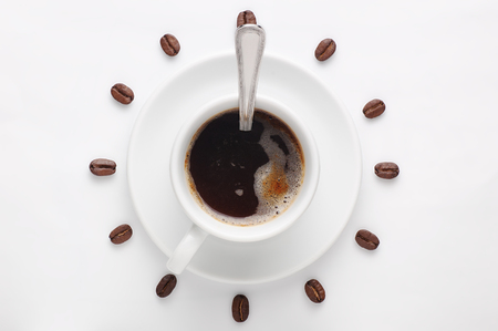Foto de Coffee cup with spoon on saucer and coffee beans against white background forming clock dial viewed from above as symbol of morning, energy and cheerfulness - Imagen libre de derechos