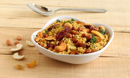Poha chivda, an Indian traditional, popular, delicious, and healthy vegetarian snack, is made from items like flattened rice, cashew nuts, peanuts, dry coconut, turmeric, and curry leaves.