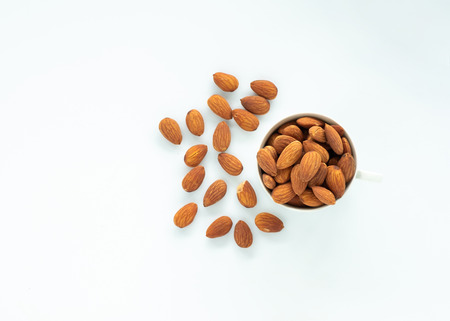 Top view of Almonds in cup on white background