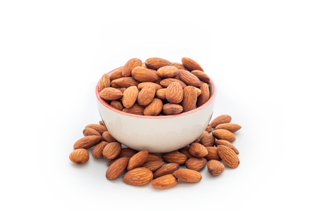 Heap almonds in cup on white background