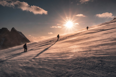 Photo for Mountaineers climbing in blizzard on snowy hill at sunset. Ryten mountain - Royalty Free Image