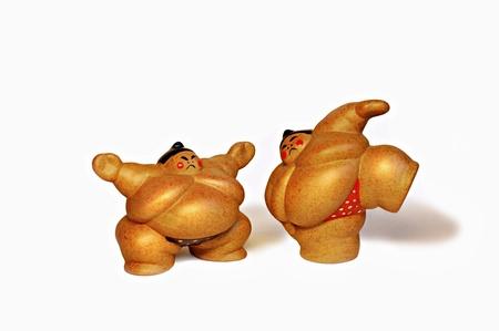 Two ceramic figures of sumo wrestlers.
