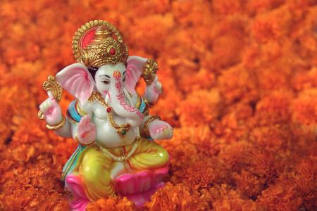 Photo pour Hindu God Ganesha with  marigold flowers - image libre de droit