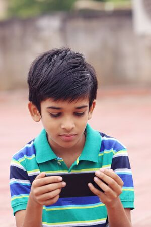 Photo for Indian Cute Little Boy With Cellphone - Royalty Free Image
