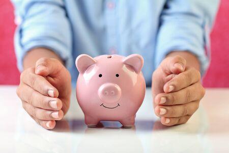 Photo pour Boy holding piggy bank for savings - image libre de droit