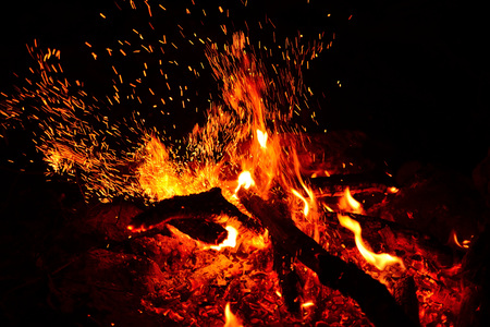 Photo for Large burning bonfire with soft glowing flame and sparkles flying all around - Royalty Free Image