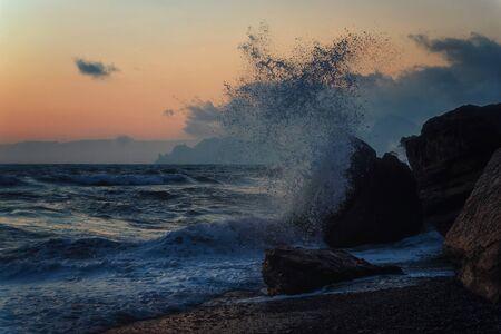 Photo pour Storm on a rocky sea coast at sunset - image libre de droit