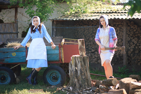 Photo pour Two young women in the village. Woman holds an ax in her hands. Portrait in retro rural style. - image libre de droit
