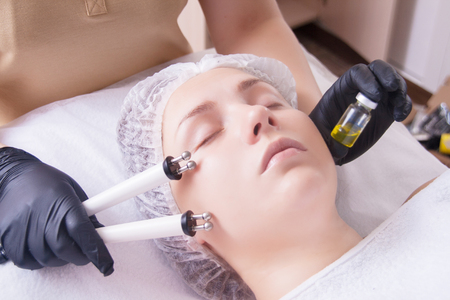 Photo pour The cosmetologist makes the apparatus a procedure of Microcurrent therapy of a beautiful, young woman in a beauty salon. Cosmetology and professional skin care. - image libre de droit