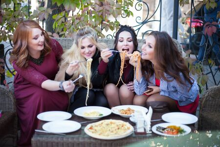 Photo pour Four young women having lunch in a cafe. Pasta in a summer cafe. - image libre de droit