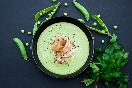 Healthy green soup with ham and peas on a black background