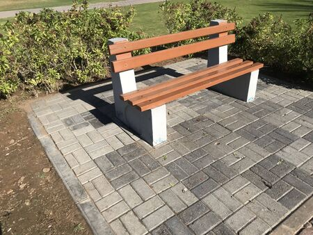 Photo pour A wooden bench with concrete supports built in between the interlock floor tile flooring isolated for a healthy and relax conversation with friend or family relative in a park or outdoor - image libre de droit