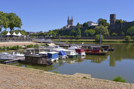 Port on the Maine river of Angers and the cathedral Saint Maurice and castle at the top of hill. Angers is a commune in the Maine-et-Loire department, Pays de la Loire Region, in western France about 300 km (190 mi) south-west of Paris