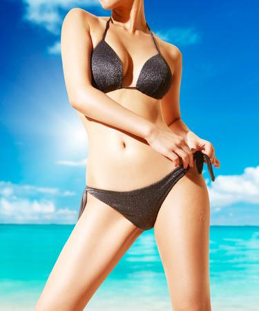 Foto de Woman with black bikini on the beach. Beautiful tanned skin. - Imagen libre de derechos