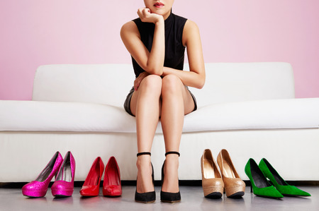 Foto de Woman choosing shoes or trouble with high heels. - Imagen libre de derechos