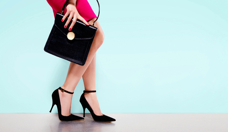 Photo for Woman fashion with beautiful black purse hand bag with high heels shoes. Copy space on light blue background. Isolated. - Royalty Free Image