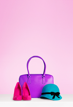 Woman fashion accessories set isolated on pink background with copy space. Leather purple hand bag, red heels, and elegant green hat made of felt.