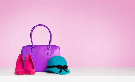Colorful woman fashion accessories on the table isolated on pink. Red heels and a blue green hat and A purple leather bag.