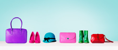 Colorful hand bags, shoes, and hat isolated on light blue background. Woman fashion accessories item. Shopping image.