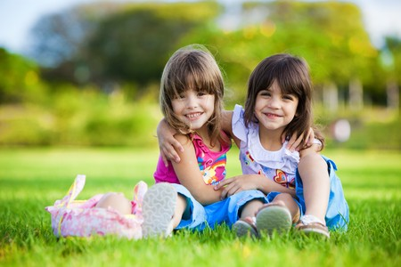 Two young smiling girls hugging each other in the grass