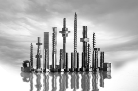 A skyline made of long screws, bolts, nuts on a white background with wild clouds