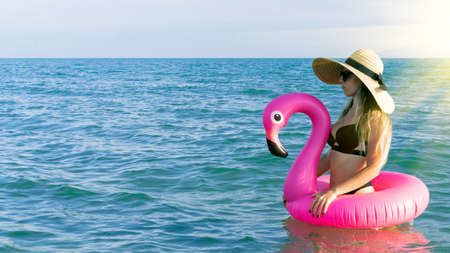 Photo pour Summer hat beach. Happy young sexy girl in bikini swimsuit, sunglasses and straw hat with pink inflatable flamingo in blue sea water on ocean background. Luxury lifestyle travel - image libre de droit