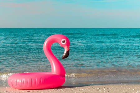 Photo pour Summer concept background. Pink inflatable flamingo in blue ocean water for sea summer beach background. Pool float party - image libre de droit