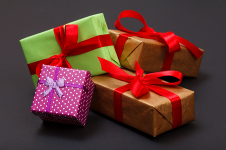 Foto de Gift boxes tied with red ribbons one on black - Imagen libre de derechos