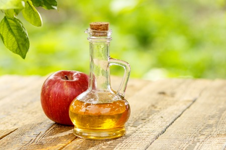 Photo for Apple vinegar in glass bottle with cork and fresh red apple on old wooden boards with blurred green natural background. Organic food for health - Royalty Free Image