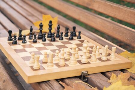 Wooden chessboard with pieces on the bench in a city park. Shallow depth of field. Focus on the white pieces.