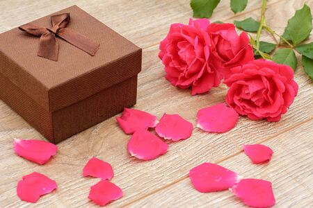 Brown gift box, rose petals and beautiful roses on the wooden background. Concept of giving a gift on holidays. Top view.