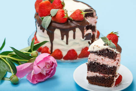 Photo for Homemade chocolate cake decorated with fresh strawberries and leaves of mint on a glass plate, a piece of cake on white plate and a peony on the blue background - Royalty Free Image