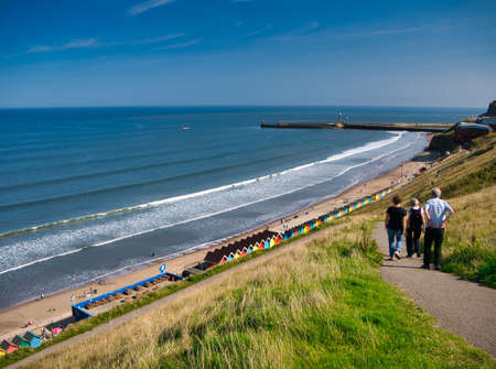 Photo pour Tourists on a path overlooking colourful beach huts, the coast and harbour piers at Whitby, North Yorkshire, UK - taken on a sunny day at the end of summer - image libre de droit