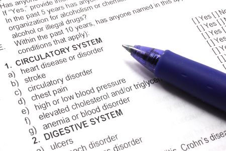 Health insurance medical questions on an application with a pen.