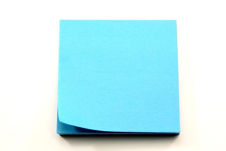 A stack of aqua blue sticky notes with the corner curling ready to be torn off and used.