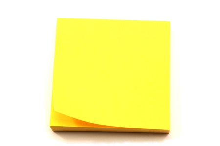 A stack of yellow sticky note pads with a corner turned up.