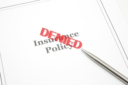 Photo pour An insurance policy and a pen and the word Denied in red stamp across the policy. - image libre de droit