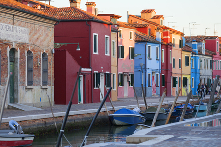VENICE ,BURANO - ITALY, SEPTEMBER  21, 2017: Colorful small, brightly painted houses on the island of Burano, reflection in the water. Burano is an island in the Venetian Lagoon, situated 7 kilometers  from Venice