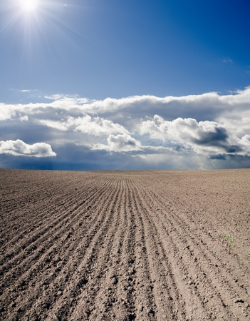 black ploughed field under blue cloudy sky with sun