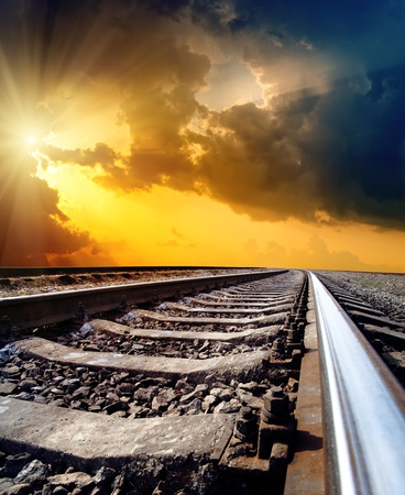 railway to horizon under dramatic sky with sun
